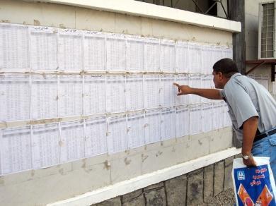 أحد الموظفين يتفحص أثناء حضوره رقم القيد في الكشوفات الموجودة لدى اللجنة