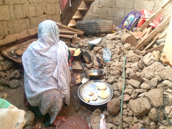 امرأة تطبخ في منزل مهدم