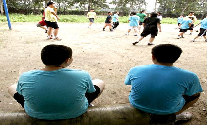 صبية يشاهدون زملاءهم بينما هم يلعبون في معسكر صيفي لخفض الوزن في الصين أرشيف