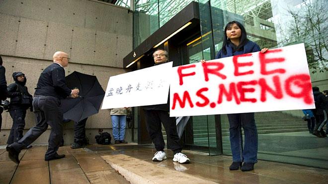 ارشيف - جيسون ردموند آدا يو (يمين) وروبرت لونغ يرفعان لافتتين تطالبان باطلاق سراح مديرة هواوي مينغ وانتشو أمام محاكم فانكوفر الكندية