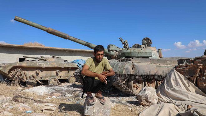 محمد النعيمي يجلس أمام دبابة لجيش العزة أثناء التدريب