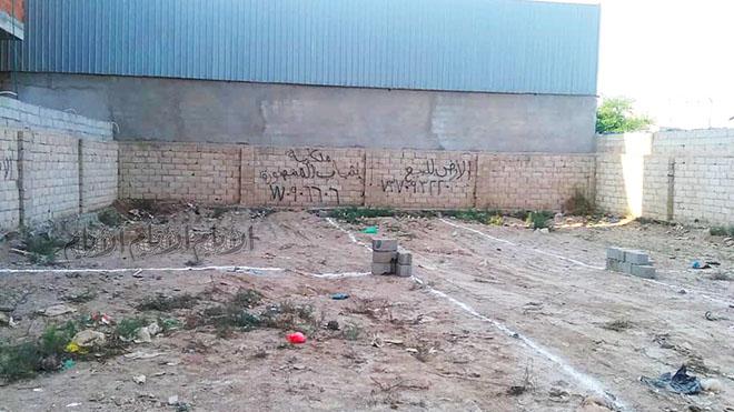 يظهر في الصورة قيام المعتدين بالكتابة على سور الأرضية وبتقسيمها من الداخل