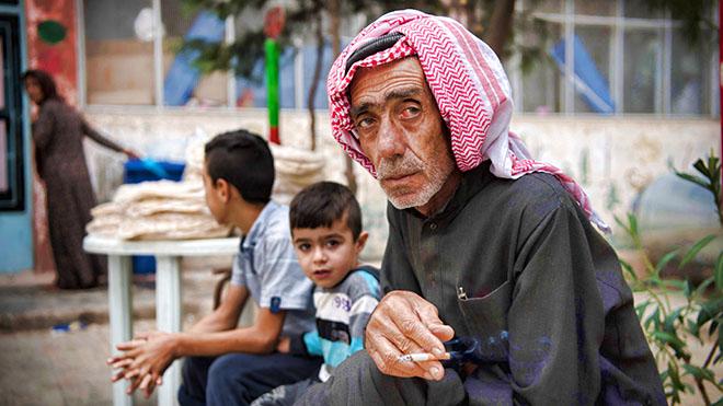 رجل سوري مهجّر يدخن داخل مدرسة تحولت إلى ملجأ للنازحين بسبب الحرب ، في بلدة الحسكة