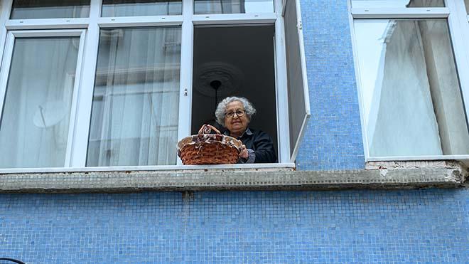لطفي يسيلباس ، امرأة تركية تبلغ من العمر 89 عامًا تعيش بمفردها في منزلها ، تخفض سلتها بينما ينتظر جارها أخذها في كاديكوي