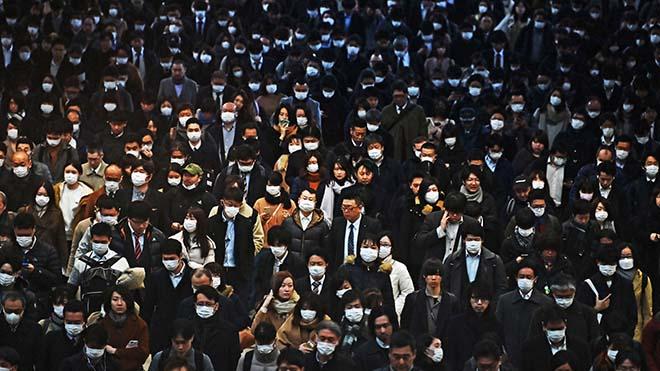 موظفون يرتدون كمامات يشقون طريقهم للعمل صباحًا في محطة قطار شيناغاوا في طوكيو