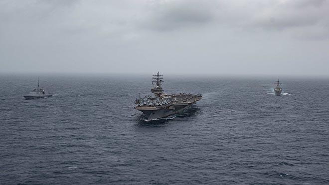 حاملة الطائرات الأمريكية، رونالد ريجان وإلى اليسار الفرقاطة الفرنسية لانغدو، يوم أمس الأول الإثنين
