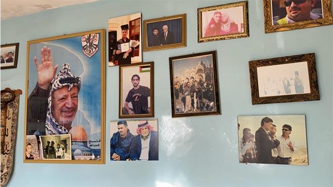 صور من منزل أم حسن بريجية وفيها أوسمة تكريم من جهات مختلفة، وصور لها ولابنها الأسير المحرر وابنها الشهيد (الجزيرة)