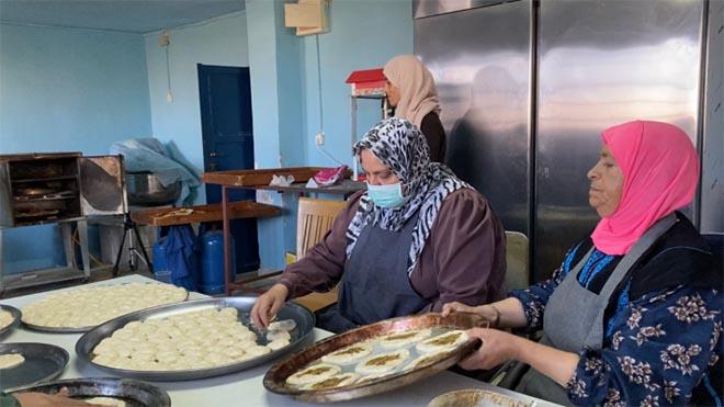 أم حسن وهي تقوم بالعمل التطوعي مع مجموعة من النساء لإعداد طعام تصفه بـ لصحي لطلبة المدارس، الذي يسهم في مساعدة النساء اقتصاديا الجزيرة