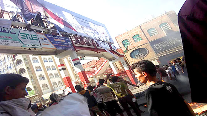متظاهرون يمزقون صورة للرئيس هادي